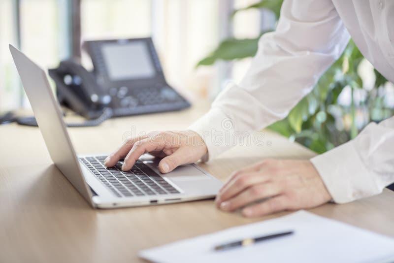 Mãos do homem de negócios que datilografam no laptop no escritório fotos de stock
