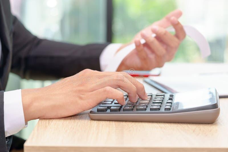 Mãos do homem de negócios que empurram a calculadora para calcular um receip imagens de stock
