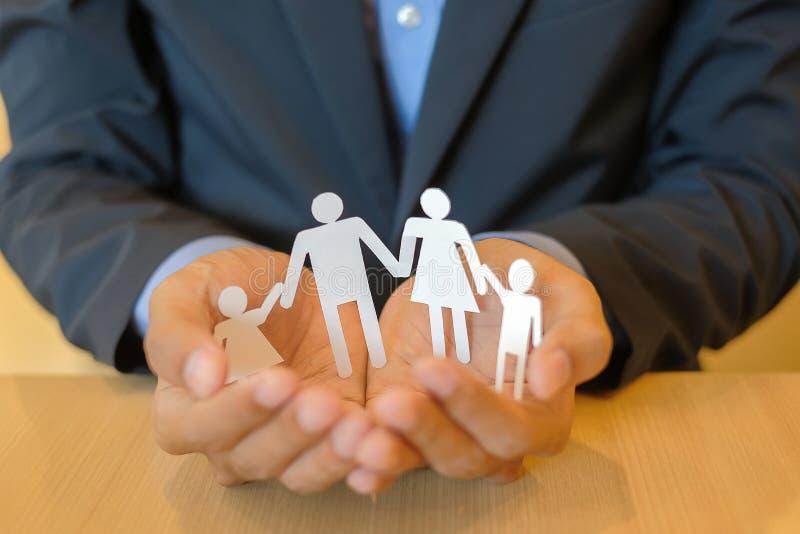 Mãos do homem de negócios que guardam o papel da família Conceito dos cuidados médicos e do seguro imagens de stock