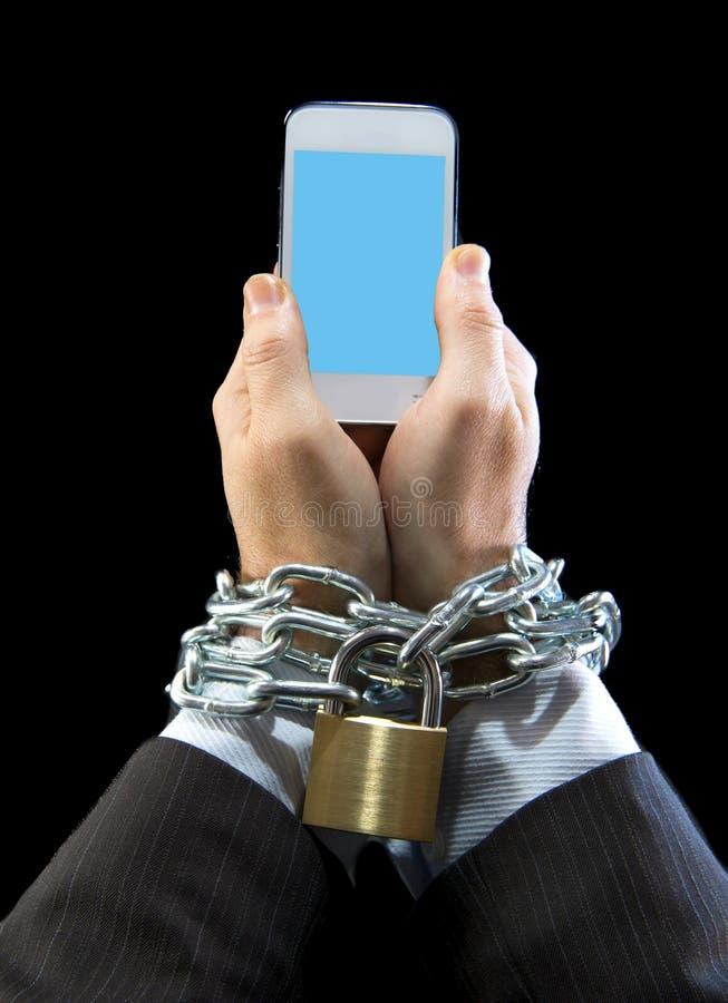 Mãos do homem de negócios viciado para trabalhar fechado e enchained no apego do telefone celular fotografia de stock royalty free
