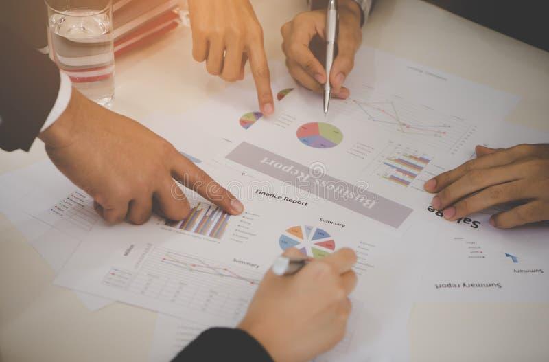 Mãos do homem e da mulher de negócio que discutem dados da venda na reunião imagem de stock