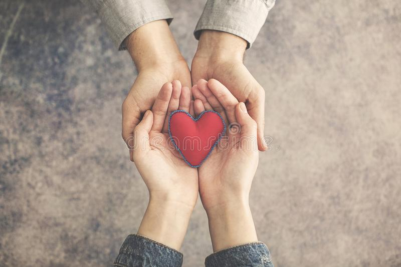 Mãos do homem e da mulher junto com o coração vermelho imagens de stock