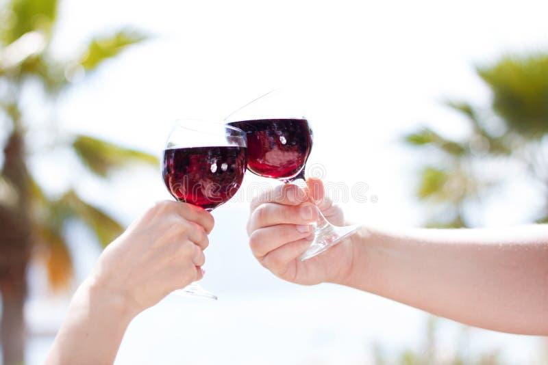 Mãos do homem e da mulher que guardam vidros do vinho tinto do suco da cereja, brindando, no fundo tropical do verão Férias do cu fotos de stock