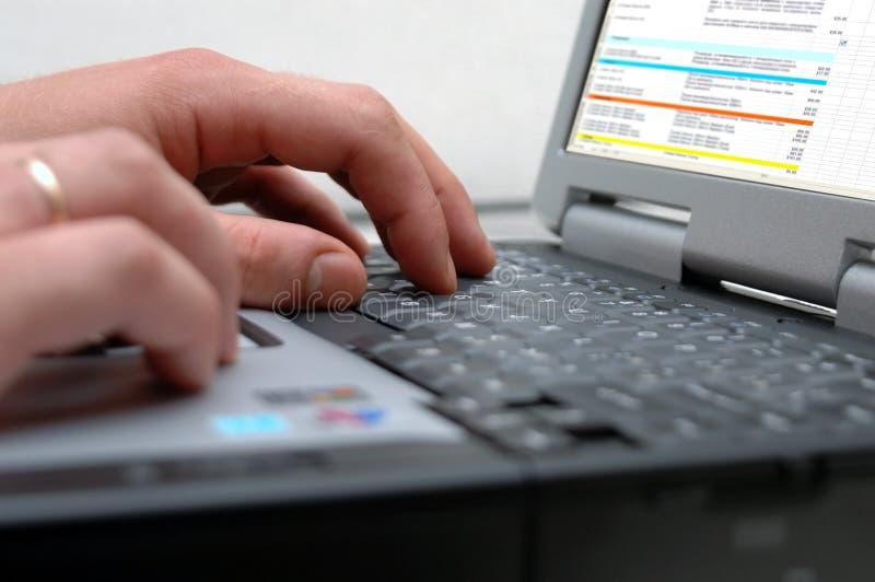 Mãos do homem no teclado do portátil fotografia de stock