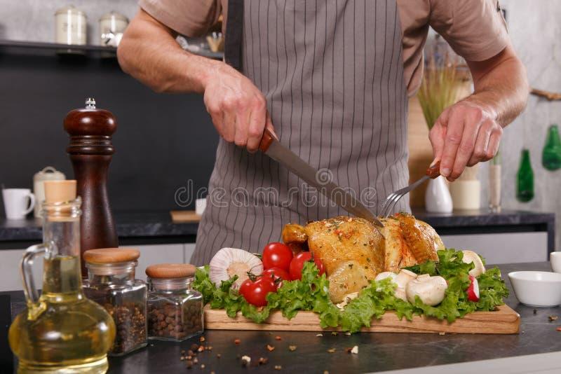 Mãos do homem principal que cuting a galinha cozida com vegetais foto de stock