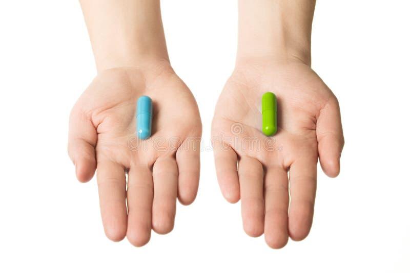 Mãos do homem que dão dois comprimidos grandes Azul e verde Faça sua seleção nervos calmos e saúde Escolha seu lado foto de stock royalty free
