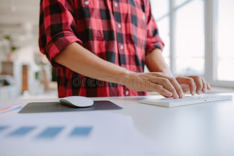 Mãos do homem que datilografam no teclado de computador fotos de stock