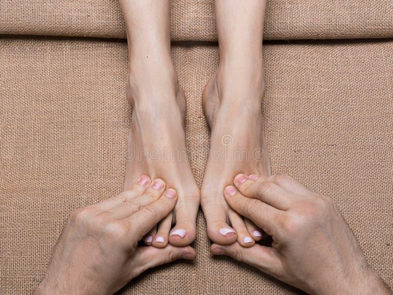 Mãos do homem que fazem massagens os pés da mulher na lona Sal?o de beleza dos termas foto de stock