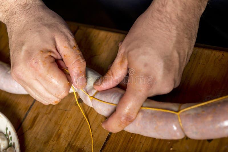 Mãos do homem que fazem o salame fotografia de stock