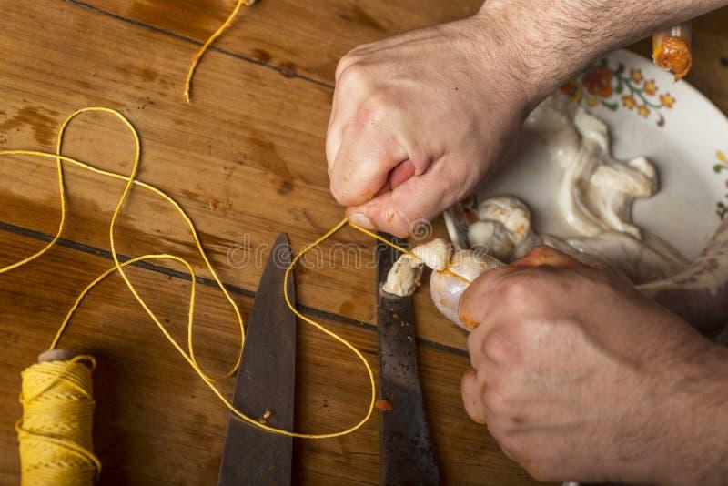 Mãos do homem que fazem o salame fotos de stock