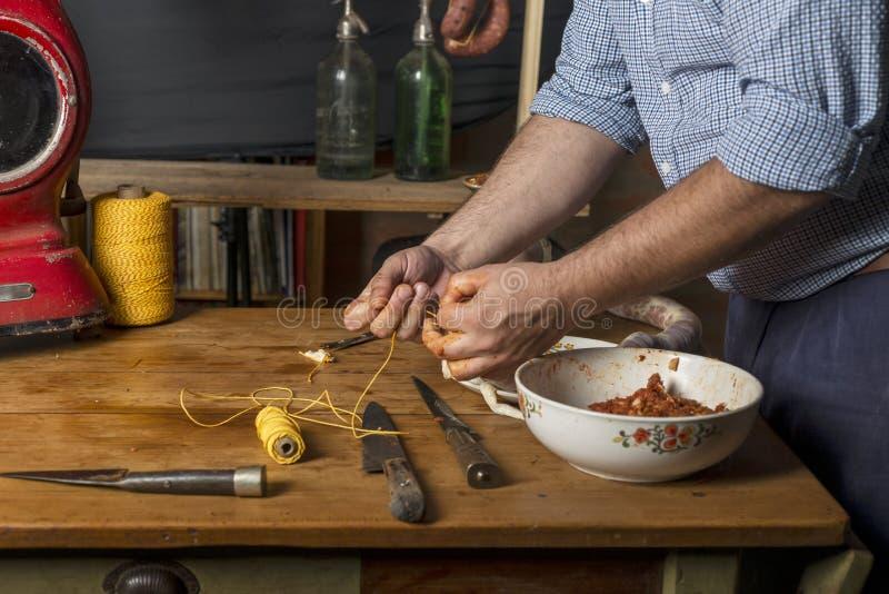 Mãos do homem que fazem o salame imagem de stock