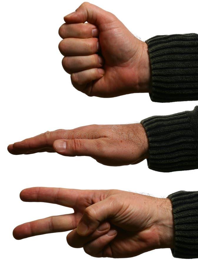 Mãos do homem que fazem a rocha, papel, tesouras imagem de stock royalty free