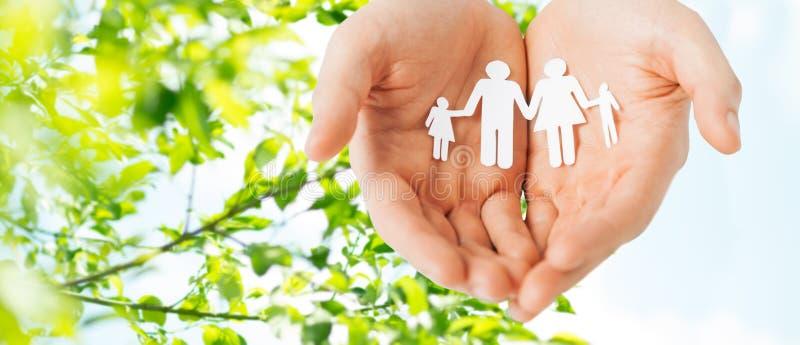 Mãos do homem que guardam o entalhe de papel da família fotografia de stock royalty free