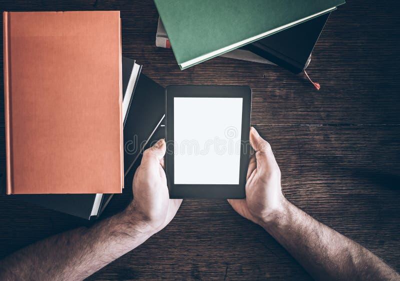 Mãos do homem que guardam o leitor do ebook entre pilhas de livros foto de stock