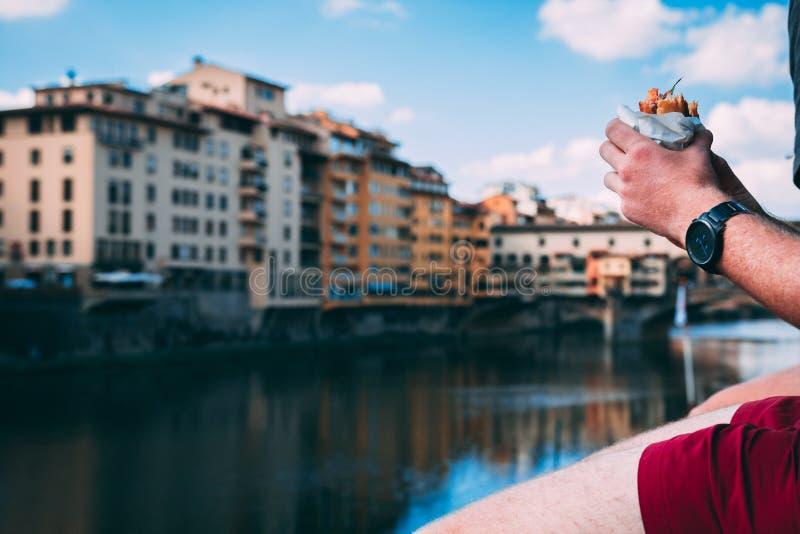 Mãos do homem que guardam o sanduíche do focaccia do panini que senta-se sobre o rio de Arno e a ponte de Ponte Vecchio imagens de stock