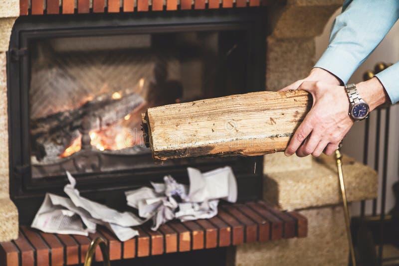 Mãos do homem que guardam a parte de madeira na chaminé dianteira fotografia de stock