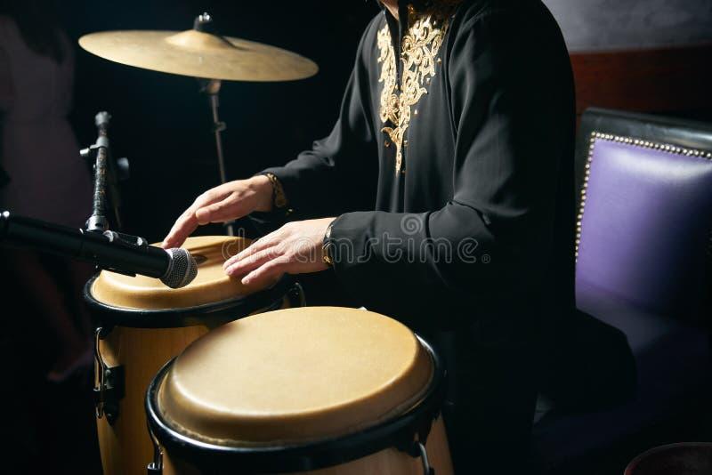 Mãos do homem que jogam a música em cilindros do djembe foto de stock