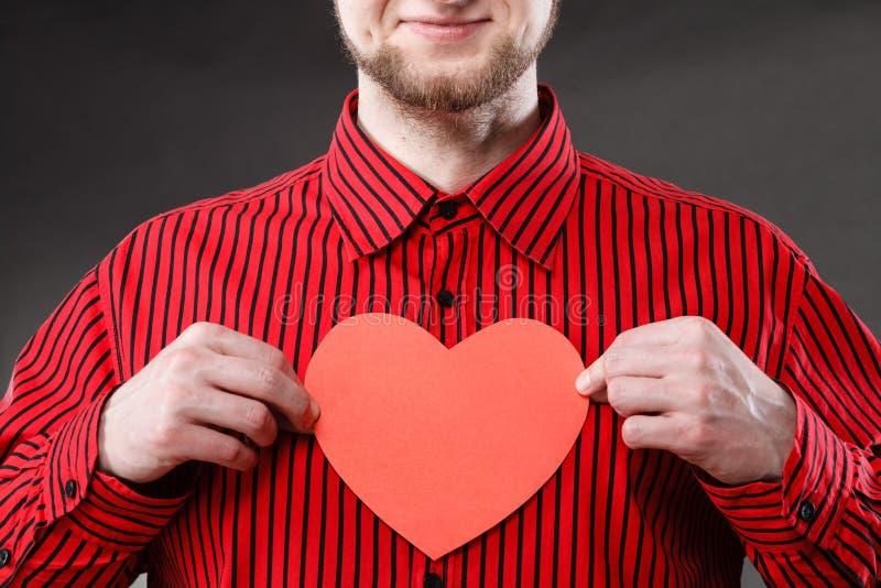 Mãos do homem que mantêm o coração feito do papel imagem de stock