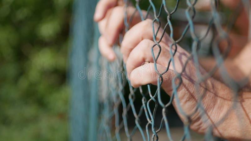 Mãos do homem que penduram em uma cerca metálica na prisão fotos de stock royalty free