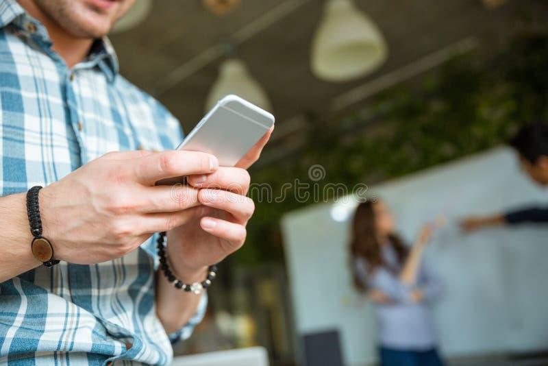 Mãos do homem que usa o telefone celular quando sua argumentação dos sócios fotos de stock royalty free