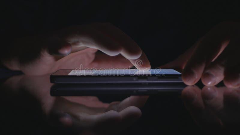 Mãos do homem usando a aplicação sem fio do telefone celular na escuridão fotografia de stock