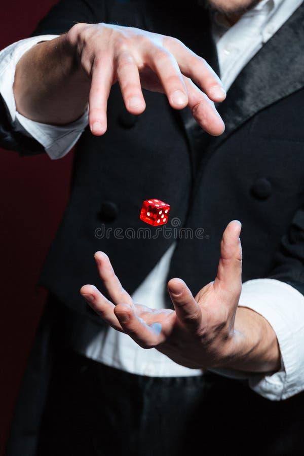 Mãos do mágico do homem que fazem o voo vermelho dos dados no ar fotografia de stock