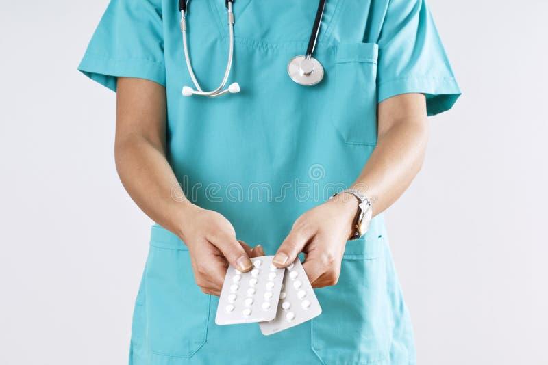 Mãos do médico da mulher que guardam os comprimidos no fundo cinzento imagem de stock