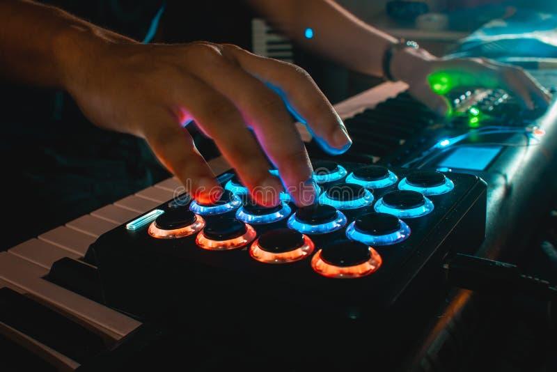 Mãos do músico que jogam um controlador da almofada de midi foto de stock