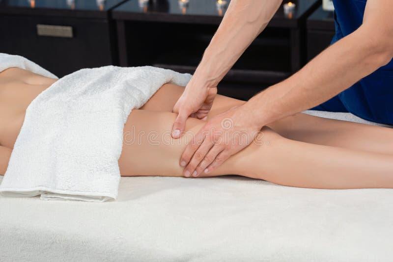 Mãos do massagista que fazem massagens o quadríceps da fêmea no salão de beleza dos termas imagens de stock royalty free