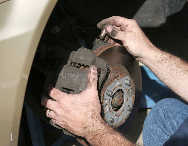 Mãos do mecânico em freios imagens de stock