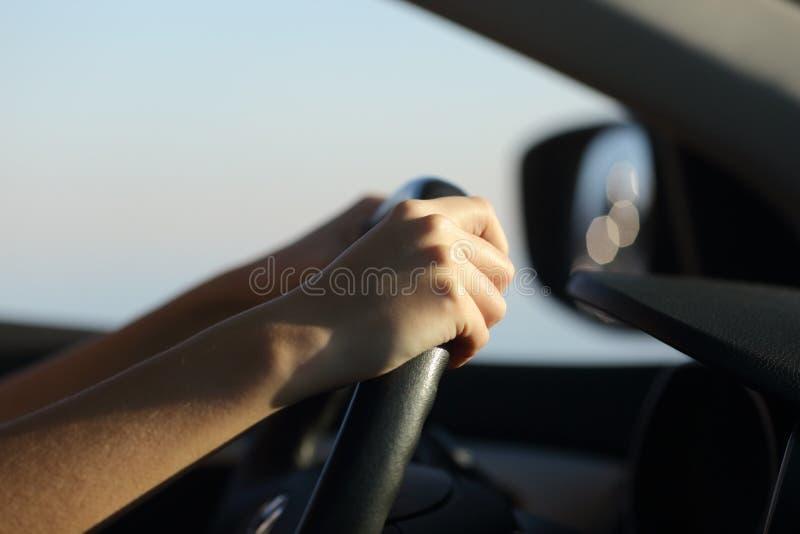 Mãos do motorista que guardam o volante que conduz um carro fotos de stock royalty free