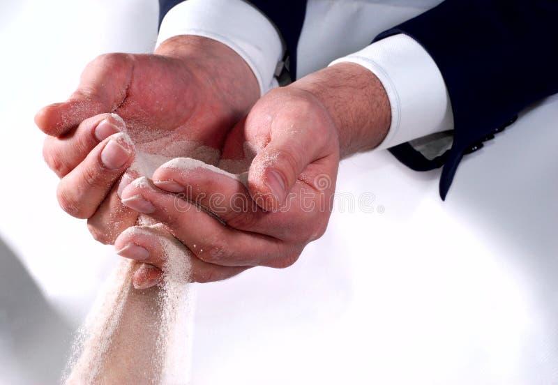 Mãos do negócio que tentam prender a areia fotografia de stock