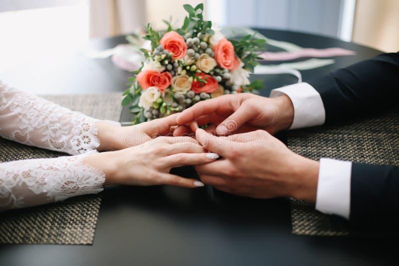 Mãos do noivo e da noiva com anéis e um ramalhete bonito do casamento imagens de stock royalty free
