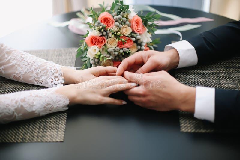 Mãos do noivo e da noiva com anéis e um ramalhete bonito do casamento fotografia de stock