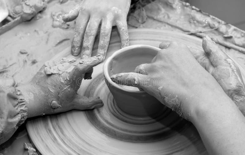 Mãos do novato e do professor na argila no processo de fazer a louça imagem de stock