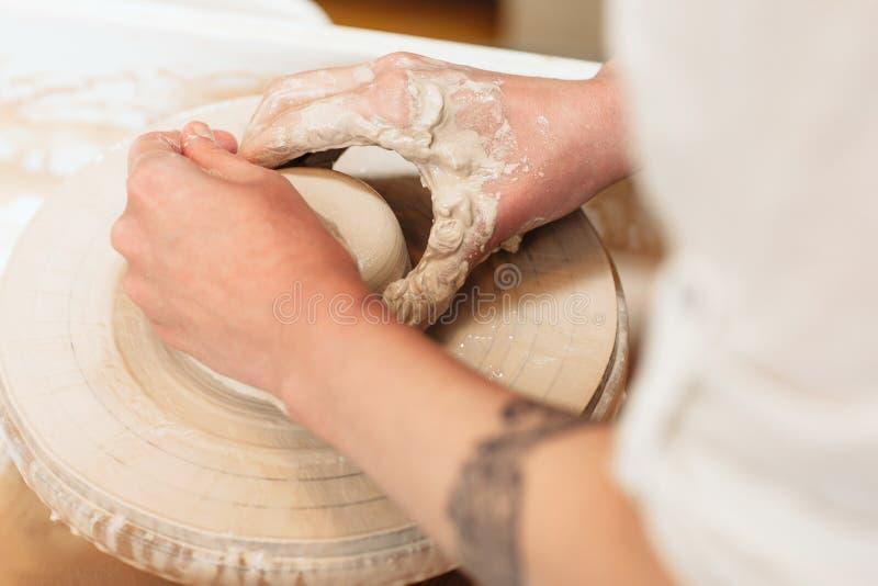 Mãos do oleiro que dão forma à opinião superior da argila fotografia de stock royalty free