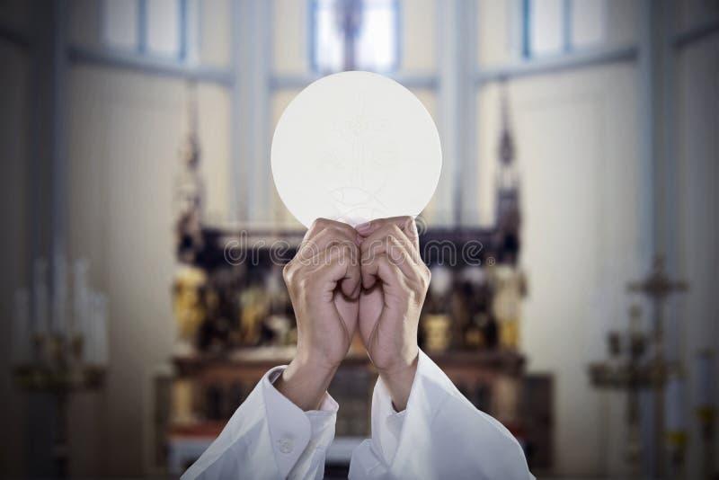 Mãos do padre para aumentar um pão do comunhão na igreja foto de stock royalty free