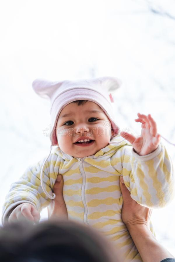 Mãos do pai que guardam uma criança de riso no ar foto de stock royalty free