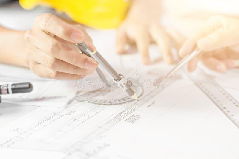 Mãos do projeto de funcionamento no modelo, conceito do coordenador da construção fotos de stock