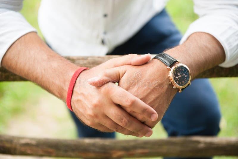 Mãos do relógio vestindo e do bracelete do homem adulto imagens de stock royalty free