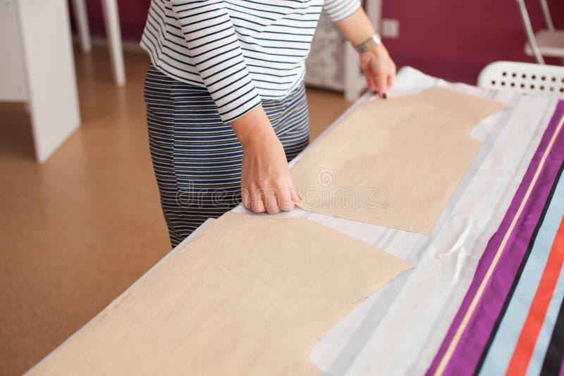 Mãos do ` s da mulher com o verniz para as unhas vermelho que palming uma parte de tecido com um teste padrão Conceito da costura imagem de stock