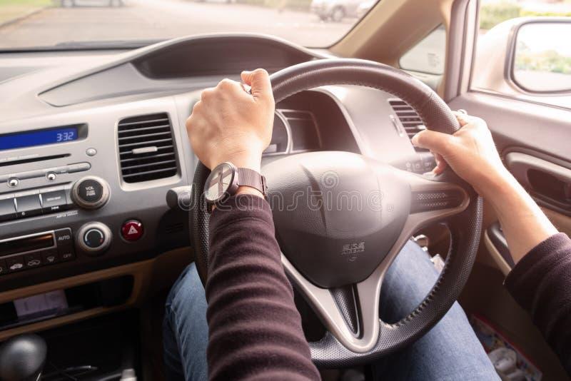 Mãos do ` s da mulher de um motorista no volante de um carro fotografia de stock royalty free