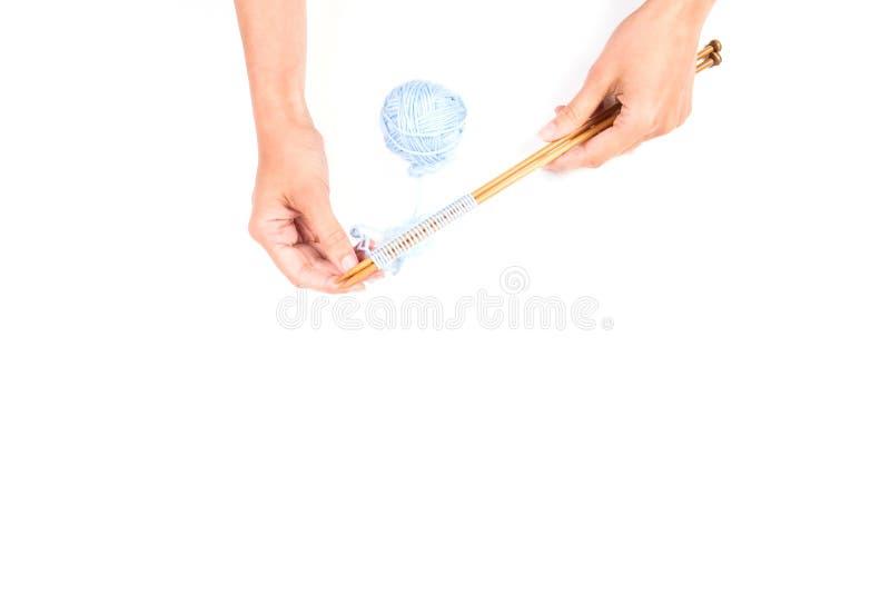 Mãos do ` s da mulher e agulhas de confecção de malhas com a bola azul do fio no fundo branco foto de stock royalty free