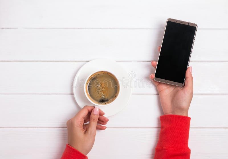 Mãos do ` s da mulher na roupa vermelha que guarda o smartphon imagens de stock royalty free