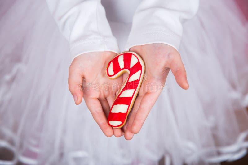 Mãos do ` s das crianças do close up que guardam o pão-de-espécie do Natal no formulário da lata do caramelo imagens de stock