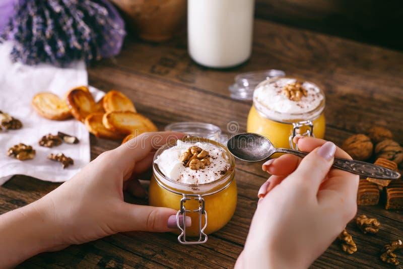 Mãos do ` s das mulheres com colher Milk shake caseiro do tarte de abóbora no frasco de vidro com chantiliy foto de stock royalty free