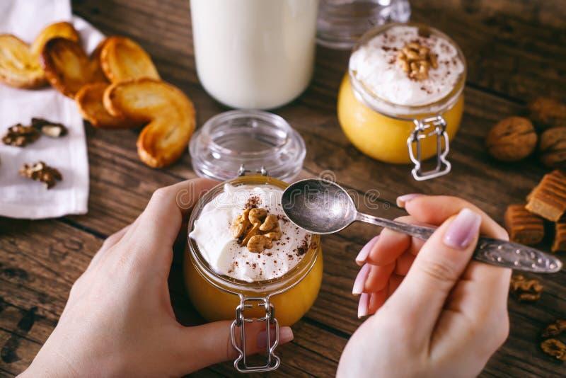 Mãos do ` s das mulheres com colher Milk shake da abóbora no frasco de vidro com as cookies do chantiliy, do caramelo, da noz e d imagens de stock