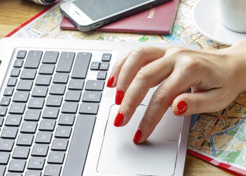 Mãos do ` s das mulheres no teclado, no passaporte, no smartphone, na câmera e no mapa do portátil fotos de stock royalty free