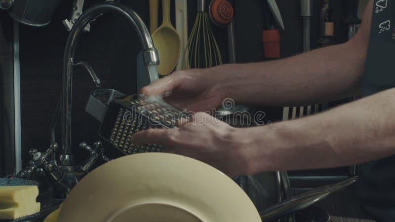 Mãos do ` s do homem que lavam pratos fotografia de stock royalty free