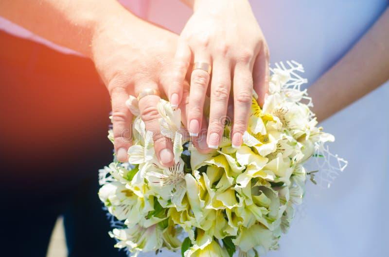 Mãos do ` s dos noivos do close-up com alianças de casamento e ramalhete Amor e união Acessórios e decoração do casamento no back fotos de stock